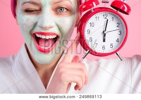 Facial Cosmetical Mask. Spa. Cosmetic Procedures. Woman With Cosmetic Mask On Face Holds Clock. Well