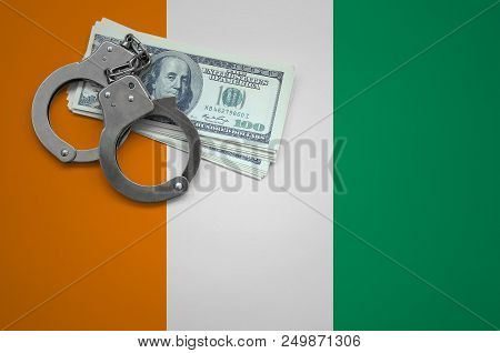 Ivory Coast flag  with handcuffs and a bundle of dollars. The concept of breaking the law and thieves crimes. poster