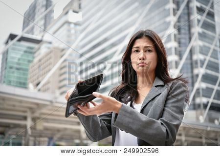 Concept Of Unemployed. Asian Businesswoman Is Opening Empty Wallet. Young Business Woman Is Stressed