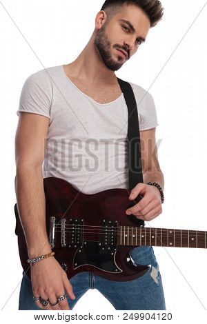 portrait of seductive young rockstar holding his electric guitar while standing on white background