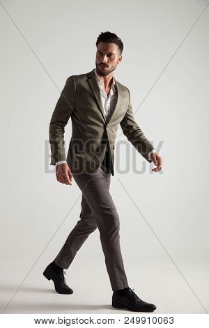 confident man in green suit walks to side on light grey background and looks back, full body picture