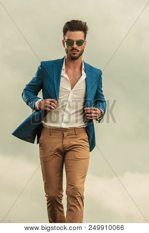 sexy man holding blue suit collar and wearing sunglasses walking on clouds background,