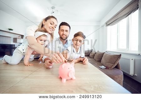 A Smiling Family Saves Money With A Piggy Bank. Happy Family At The Table In The Room.