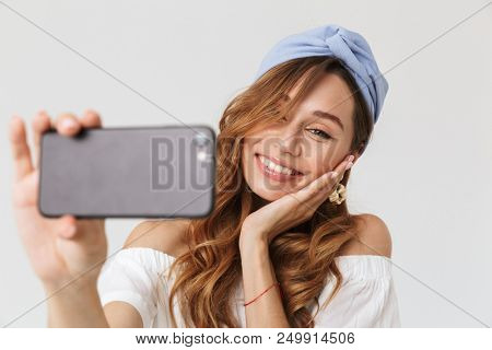Image of content beautiful woman 20s smiling while taking selfie on smartphone isolated over white background