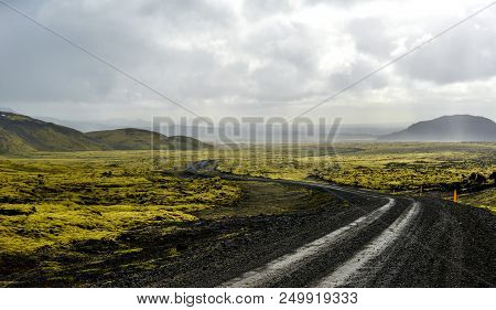 Icelandic Lava Landscape, Road And Distant Mountains