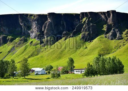 Cliffs And Mountains With Houses In The Foreground In Iceland