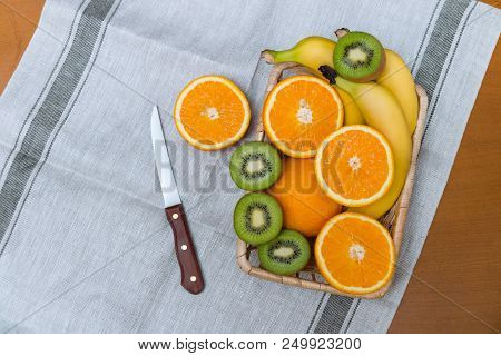 Fresh Fruits In Basket And Knife. Top View. Place For Text.