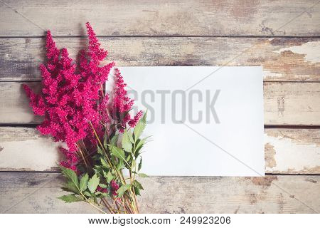 Beautiful Astilbe Flowers And Empty Card For Your Text On Aged Wooden Background