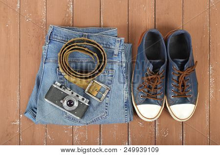 Clothes, Shoes And Accessories - Top View Old Camera, Leather Belt, Gumshoes And Blue Jeans On A Woo
