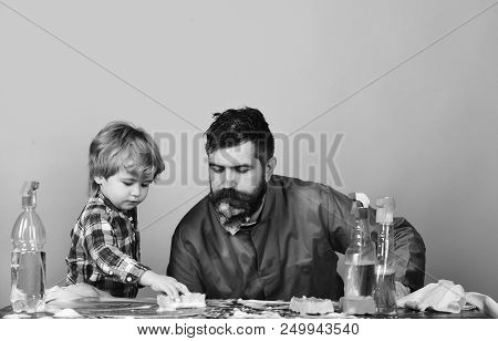 Child In Checkered Shirt Carefully Wipe Table By Sponge And Father Looking With Attention. Guy With