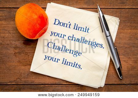 Do not limit your challenges. Challenge your limits. Inspirational handwriting on napkin with a fresh apricot.