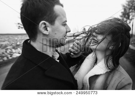 Sensual Bride With Windy Hair And Groom Embracing On Road. Happy Couple Hugging  And Kissing In Wind