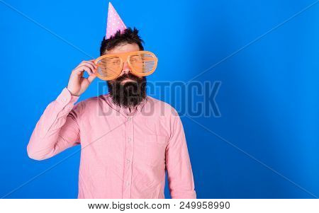 Man With Beard And Mustache On Calm Face Lonely On His Birthday, Blue Background. Guy In Party Hat C