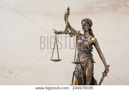 The Statue Of Justice Themis Or Iustitia, The Blindfolded Goddess Of Justice Against Marble Wall Bac