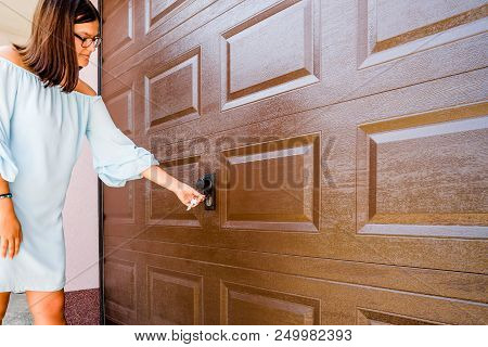 Girl Or Young Woman Puts Key In The Keyhole Of Garage Door Pvc