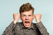 emotional breakdown. angry enraged infuriated crazy man screaming. portrait of a young guy on light background. emotion facial expression. feelings and people reaction. poster