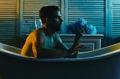 Guy in bathroom covered with foam with toiletries on background. Macho sitting naked in bathtub and looking at sponge. Man with beard and concentrated face. Sex and erotica concept. poster