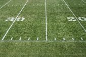 View of a grassy football field with yardage markers poster