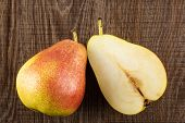 Group of one whole one half of fresh red pear forelle variety flatlay on brown wood poster