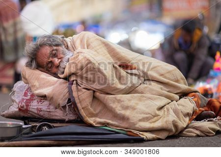 PURI, INDIA, JANUARY 13, 2019 : A homeless man is sleeping in the street of the Puri outdoor market.