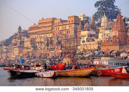 VARANASI, INDIA, JANUARY 18, 2019 : Sunrise scenery on Varanasi ghats and Ganga river banks with tourist boats.