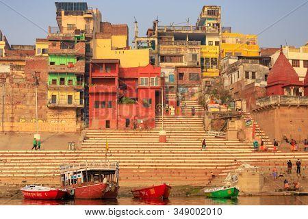 VARANASI, INDIA, JANUARY 18, 2019 : Warm sunrise colors over Varanasi ghats and colofrul buildings.