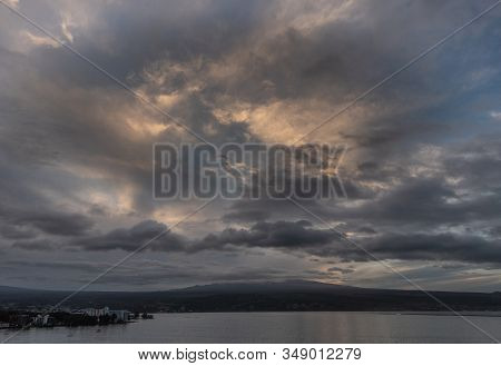Hilo, Hawaii, Usa. - January 14, 2020: Spectacular Dark Evening Cloudscape With Yellow Sunlight Patc