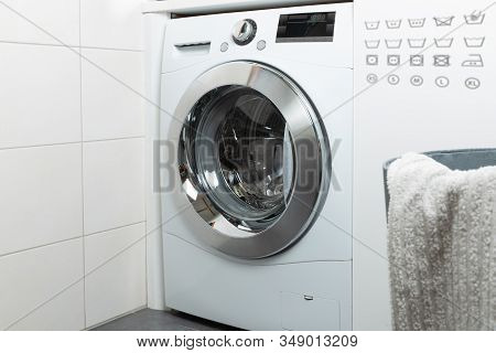 Cleaning And Loading White Washing Machine  In A Natural Light