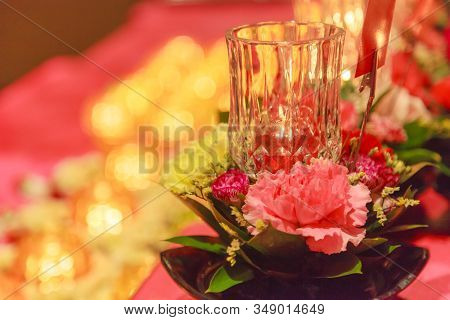 Lighting Candle and Offering Fresh Blossoming Flowers before Buddha Image believed to bring good merits to sincere Buddhist prayers. Religion, Buddhism, Faith, Spirituality, Belief and Ritual concept poster