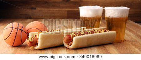 Grilled Hot Dogs With Mustard And Ketchup On The Table With Draft Beer. Television Watching Basketba