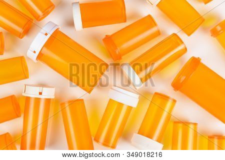Closeup flat lay group of empty plastic orange prescription bottles on their side, some with lids some without, on white.