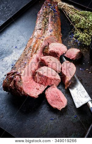 Barbecued dry aged venison tenderloin fillet steak and saddle natural with herbs offered as closeup on a rustic metal tray