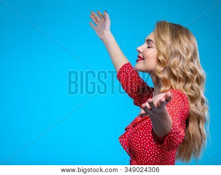 Young happy blonde woman with raised hands. Beautiful girl with raised arms up. Caucasian cheerful woman raising hands up. Hands up. Model in a red shirt poses in the Studio.