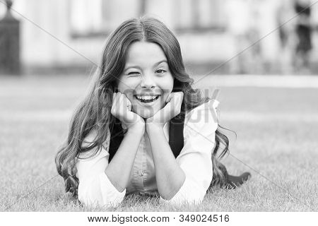 Winking To You. School Break For Rest. Adorable Pupil. Girl Kid Laying Lawn. Girl School Uniform Enj
