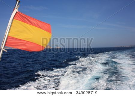 A Spanish Flag Any Striped Or Lozenges On A Background Of Blue Sea Moved By The Contrails Of The Eng