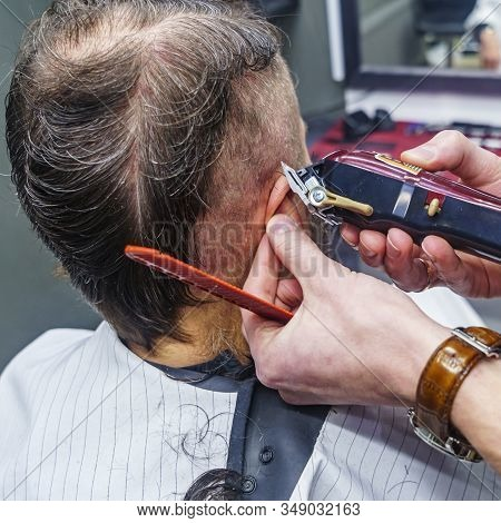 Creating A Close-up Of A Mans Haircut, A Hairdresser Cuts His Hair With A Haircut And A Comb. Barber
