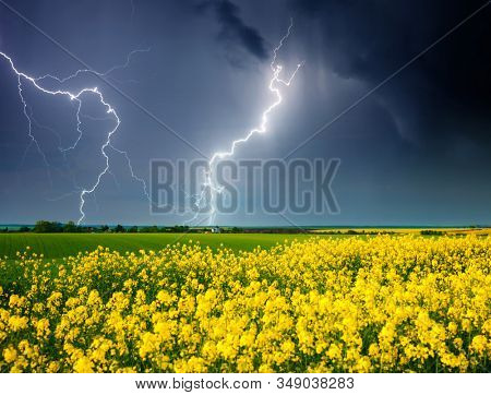 Ominous storm clouds are highlighted by lightning over field. Rural area in springtime. Exotic wallpaper of moody weather. Photo of climate change. Location place of Ukraine, Europe. Beauty of earth.