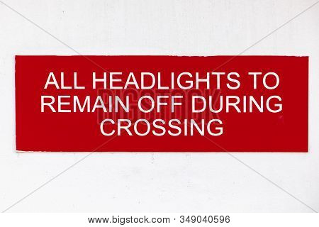 Signboard Asking Passengers Of A Ferryboat To Keep All Headlights Off During The Cruising. Red Backg