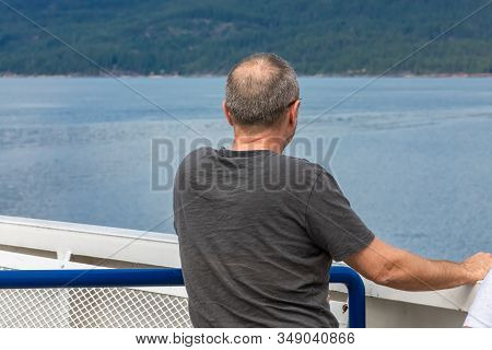 Close Up Shot From Behind Of An Aged Male Passenger Of A Ferryboat Navigating In A Canadian Lake. Ma