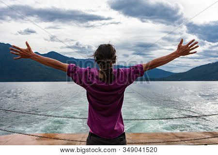Close Up From Behind Of A Man On The Deck Of A Passenger Ferryboat. Arms Wide Open In Enthusiastic A
