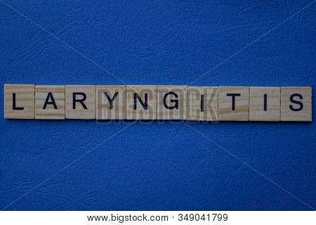 Gray Word Laryngitis From Small Wooden Letters On A Blue Table