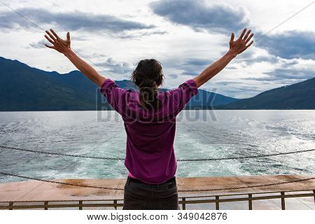 Close Up From Behind Of A Man On The Deck Of A Passenger Ferryboat. Arms Raised In Enthusiastic Appr