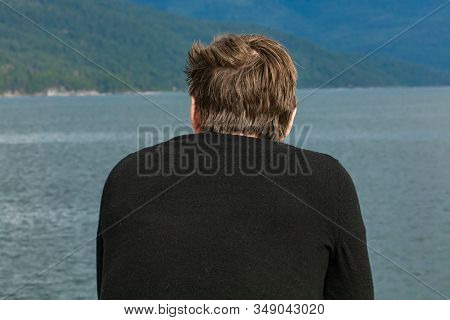 Close Up Shot From Behind Of A Young Fair Haired Man A Ferryboat Navigating In A Canadian Lake. Pass
