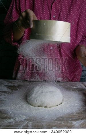 The Woman Sprinkles The Dough From The Satiated For The Flour, The Vocifa Bursts And The Falling Flo