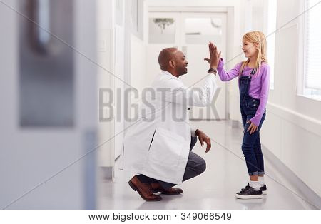 Male Paediatric Doctor Giving Young Girl Patient High Five In Hospital Corridor