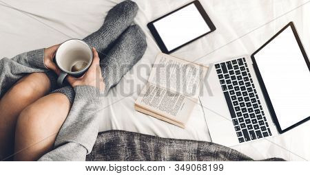 Young Woman Relaxing And Drinking Cup Of Hot Coffee Or Tea Using Laptop Computer On A Cold Winter Da
