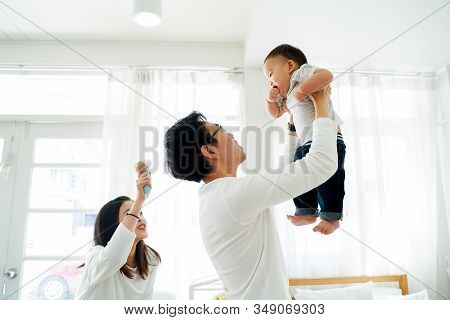 Asian Father And Mother As Married Couple Lifts Their Own Son Up And Flies Up In The Air With Laught