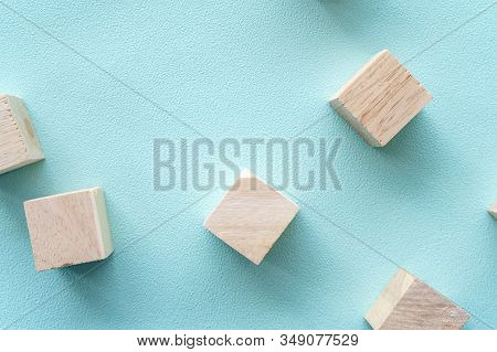 Wooden Cubic On Plastel Color Texture Background.