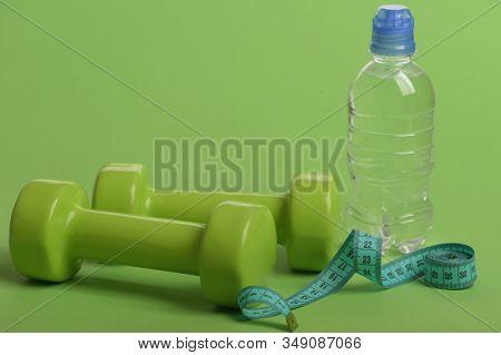 Sport And Healthy Regime Equipment. Bottle Near Roll Of Ruler
