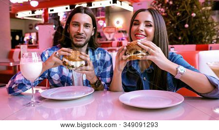 Fashionable People In The Restaurant Eating Together Some Tasty Meaty Burgers Sauce. Young Guy And P